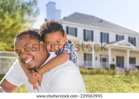 Happy Playful African American Father and Mixed Race Son In Front of House. - stock photo