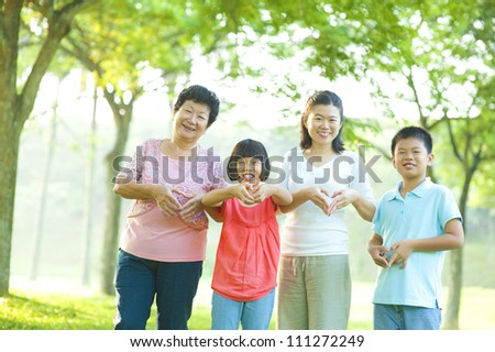 Happy playful Asian family forming love shape at outdoor green park - stock photo