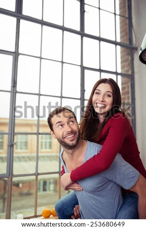 Happy playful couple enjoying a piggy back ride indoors in their apartment laughing happily as they pose in front of a large window with urban view - stock photo