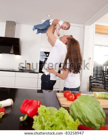 Happy playful family in kitchen - father mother and toddler son - stock photo