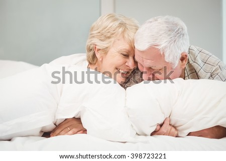 Happy playful senior couple resting in bed at home - stock photo
