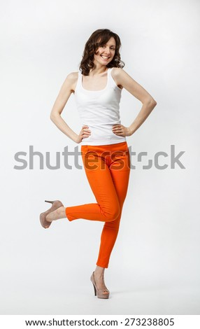 Happy playful young woman in orange pants posing on neutral background, full length studio portrait - stock photo