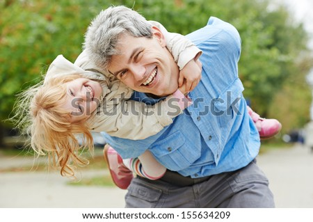 Happy playing father and daughter outdoors - stock photo