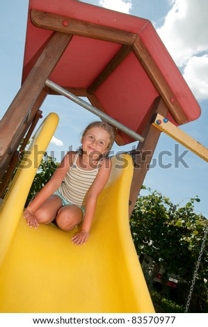 Happy playing - little girl on the playground - stock photo