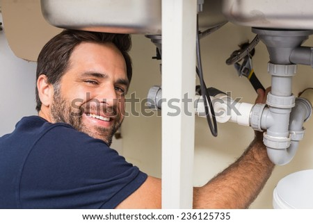 Happy plumber fixing under the sink in the kitchen - stock photo