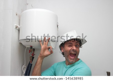 Happy plumber installing an electric water heater - stock photo