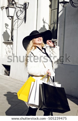 Happy plus size woman holding shopping bags on street