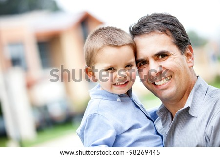 Happy portrait of a father and son smiling - outdoors - stock photo