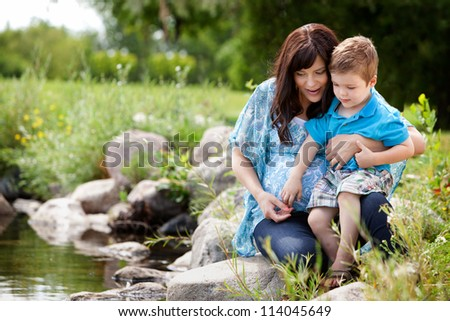 Happy portrait of a mother and son playing by a lake in a park