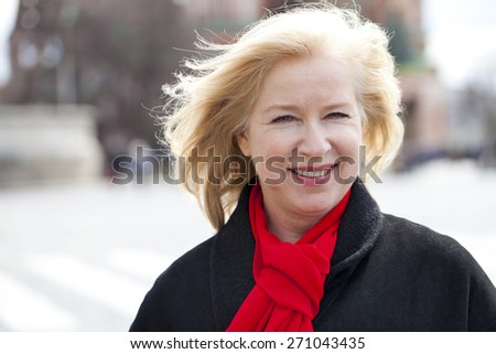Happy portrait of an elderly blonde woman, spring on the street - stock photo