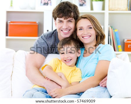 Happy portrait of beautiful smiling family with little son - indoors