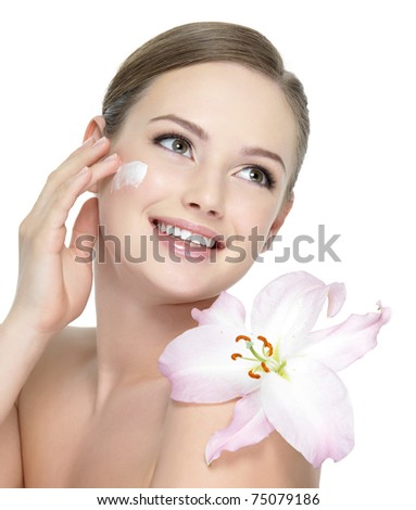 Happy portrait of beautiful young woman with flower on a shoulder applying cosmetic  cream on a cheek - isolated on white - stock photo