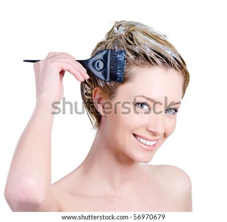 Happy portrait of cheerful beautiful young woman with brush coloring her hair - isolated on white - stock photo