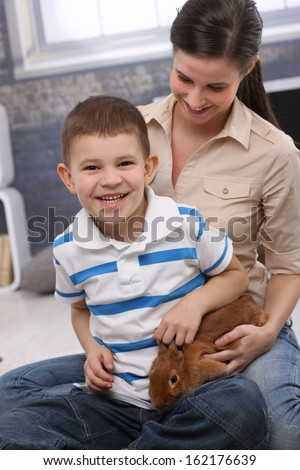 Happy portrait of laughing preschooler boy with mother playing with pet bunny at home. - stock photo