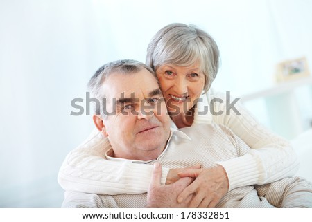 Happy portrait of senior couple, woman embracing her husband - stock photo
