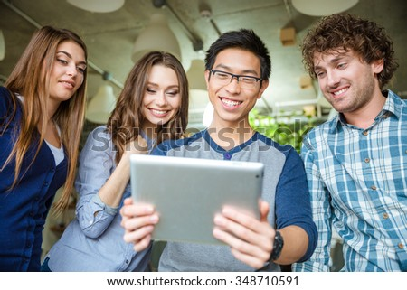Happy positive attractive people looking on the screen of tablet and smiling - stock photo