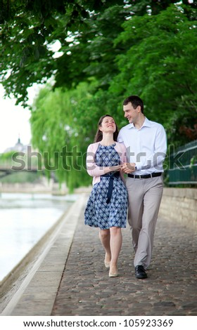 Happy positive couple is walking together by the Seine - stock photo