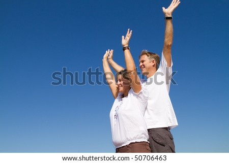 happy positive mature couple arms open, background is blue sky - stock photo