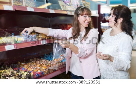 Happy positive smiling female buyers selecting traditional candies at grocery  - stock photo
