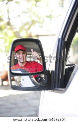 happy postal delivery courier in a van, rear view mirror perspective - stock photo