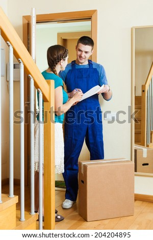happy postman in uniform delivered parcel to girl at home - stock photo