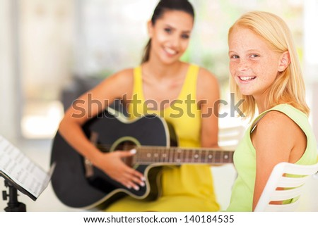 happy pre teen girl in music class with teacher - stock photo