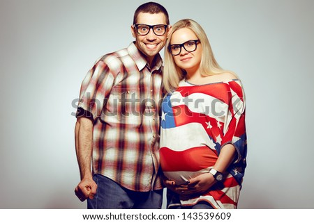 Happy pregnancy concept: portrait of two funny hipsters (husband and wife) in trendy glasses and clothes. Wife holding her belly and husband getting crazy of being father. Studio shot - stock photo