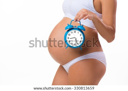 Happy pregnancy. Pregnant belly with alarm clock. Conceptual image. Soon birth. Fetal development by months - stock photo