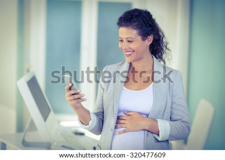 Happy pregnant businesswoman using mobile phone in office - stock photo