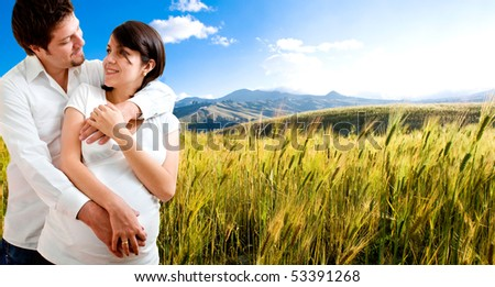 Happy pregnant couple at beautiful sunny day - stock photo