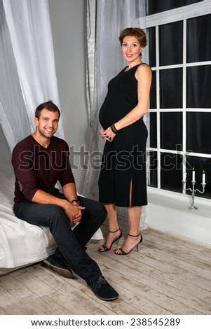 Happy Pregnant Couple dressed in black embrace each other by the window. Young parents. Happy people in white interior. - stock photo