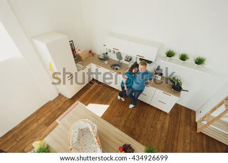 Happy pregnant couple in the kitchen. Prepare for birth and family life. Fun and hug. Love each other - stock photo