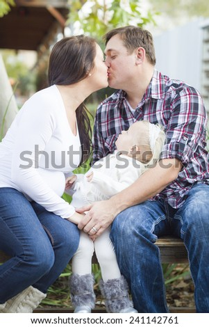 Happy Pregnant Couple Kisses Outside as Baby Girl Watches. - stock photo