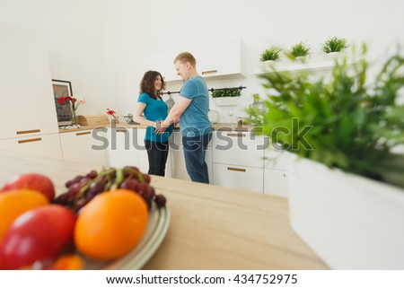 Happy pregnant couple of vegetarians in the kitchen. Prepare vegetables and having fun, hugging. Love each other