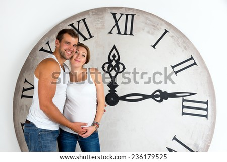 Happy Pregnant Couple on white background with giant clock. - stock photo
