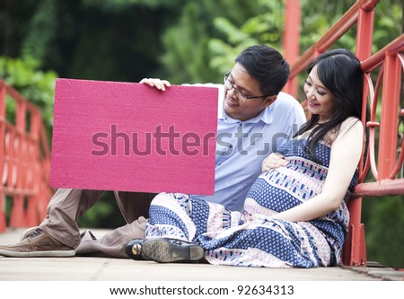 Happy pregnant couple sitting while looking at a red blank board - stock photo