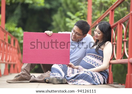 Happy pregnant couple sitting while looking at a red blank board