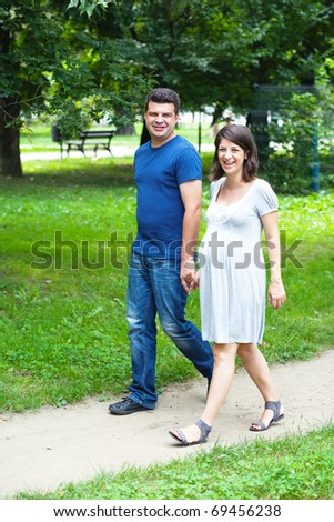 Happy pregnant couple walking in park - stock photo