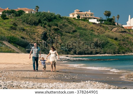 Happy pregnant couple with their son enjoying sunny day and walk on the coast in Spain. - stock photo