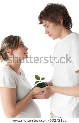 Happy pregnant family with green defenceless sprout on a white background. Concept of birth. - stock photo