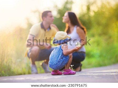 Happy pregnant family with little daughter spending time together in summer nature - stock photo
