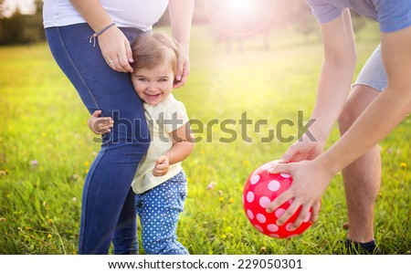 Happy pregnant family with little girl having fun playing with ball in summer nature - stock photo