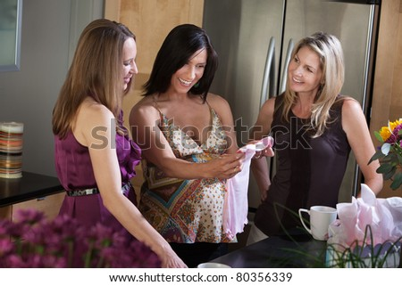 Happy pregnant lady holds baby clothes with friends in kitchen