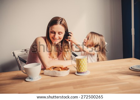 happy pregnant mother and baby daughter having breakfast at home - stock photo