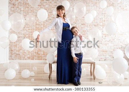 Happy pregnant mother and son under a lot of white helium balloons. - stock photo