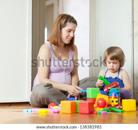 Happy pregnant mother plays with child in home interior
