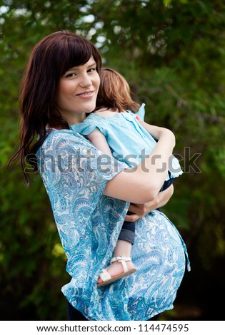 Happy pregnant mother with toddler daughter in park - stock photo