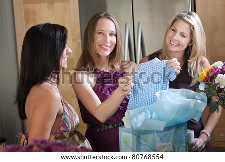 Happy pregnant woman and friends with boy baby clothes gift
