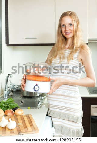 Happy  pregnant woman cooking vegetables and salmon in electric steamer