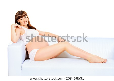 Happy pregnant woman having a rest on a sofa. Isolated over white.